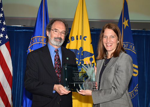 Jeffery Schloss and receives the HHS Career Achievement Award from Secretary Sylvia Burwell